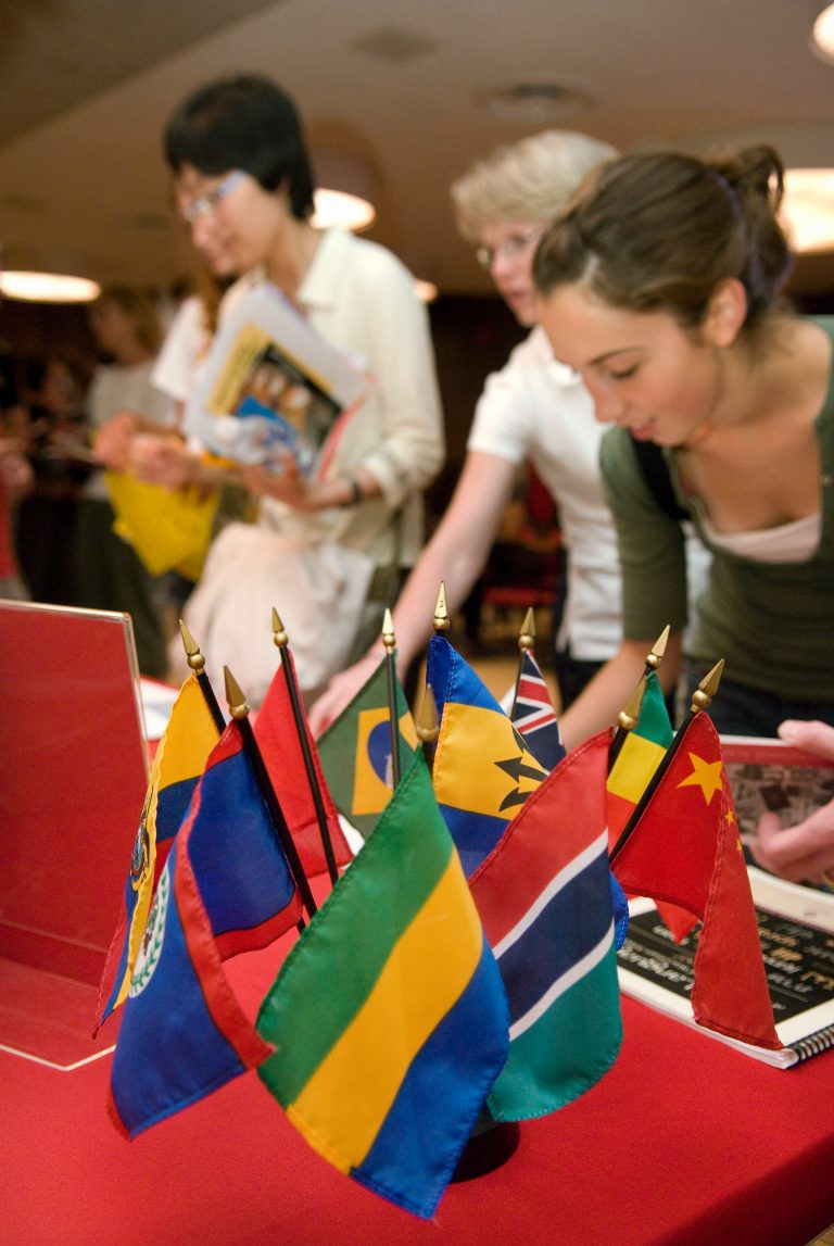 students placing flags from around the world on a table